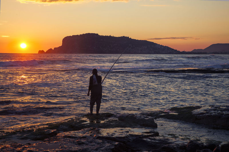 Rear view of silhouette man fishing in sea at sunset