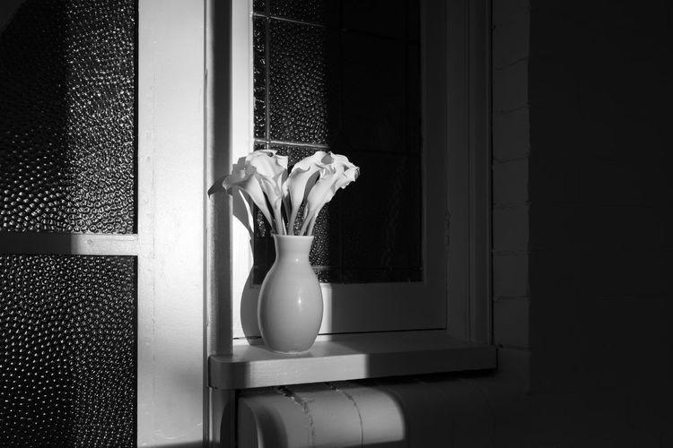 Black and white image of calla lilies in vase on window sill with moody light and hard shadows