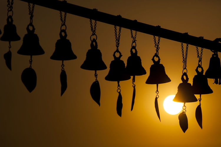 Close-up of silhouette lanterns hanging on tree at sunset