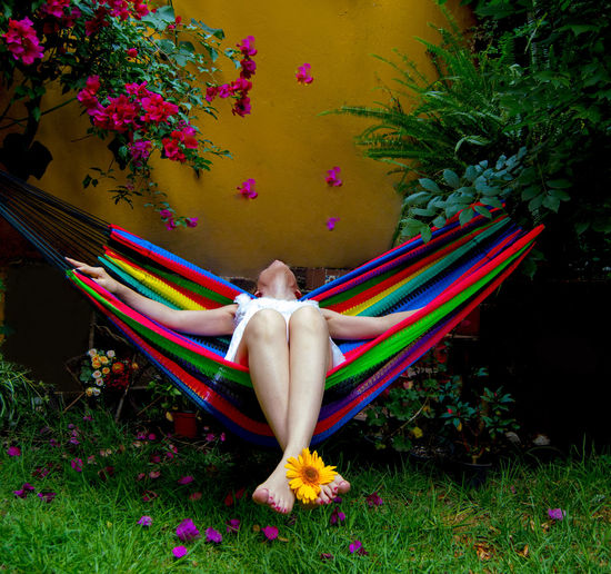 High angle view of woman relaxing on grass in yard