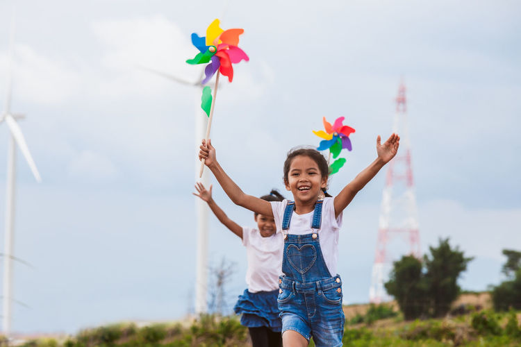 Sisters playing with pinwheel toys on land with windmills in background