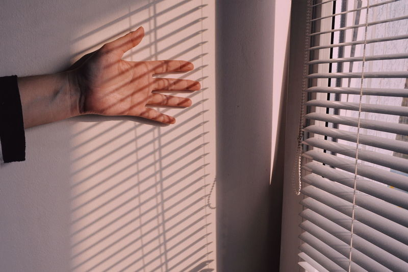 Close-up of hand on wall by window