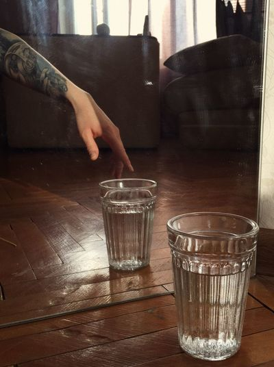 Close-up of hand holding drink on table at home