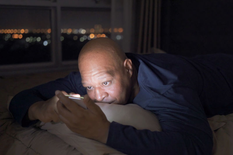 Bald man using mobile phone while lying on bed at home