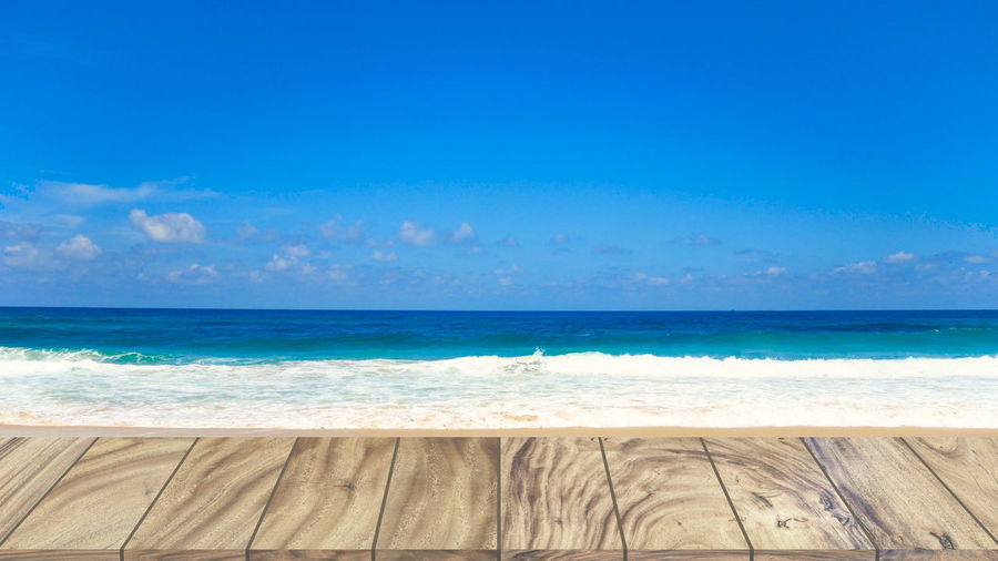Wood table on beach sea in the summer. Sea Water Beach Horizon Over Water Land Horizon Scenics - Nature Beauty In Nature Sky Wave Motion Nature Aquatic Sport Day No People Blue Sport Tranquility Tranquil Scene Outdoors Turquoise Colored