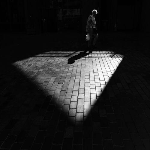 City Dark Footpath Full Length Leisure Activity Lifestyles Men Motion Nature Outdoors Paving Stone People Real People Shadow Sidewalk Street Sunlight Tiled Floor Walking Women