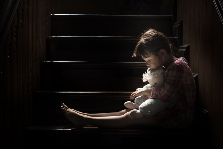 Cute girl looking down holding stuffed toy sitting on staircase at home