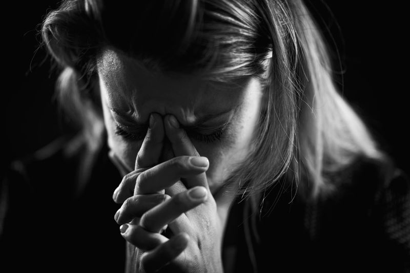 Close-up of depressed woman against black background