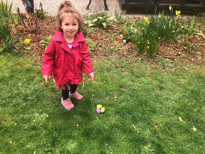 Portrait of girl pointing at easter eggs on grassy field