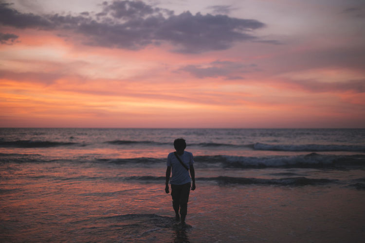Man walking at beach during sunset
