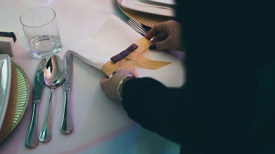 Midsection Of Woman Arranging Napkin On Table