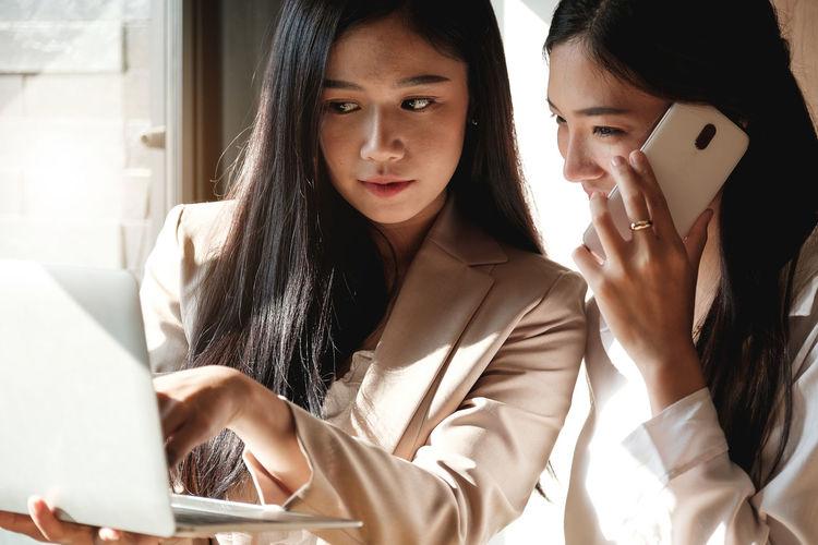 Businesswomen using technologies in office