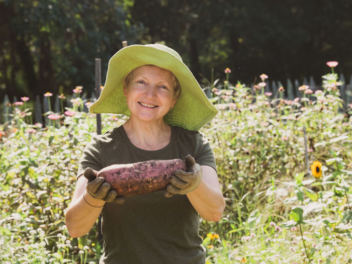 Portrait of a smiling young woman holding fresh plants