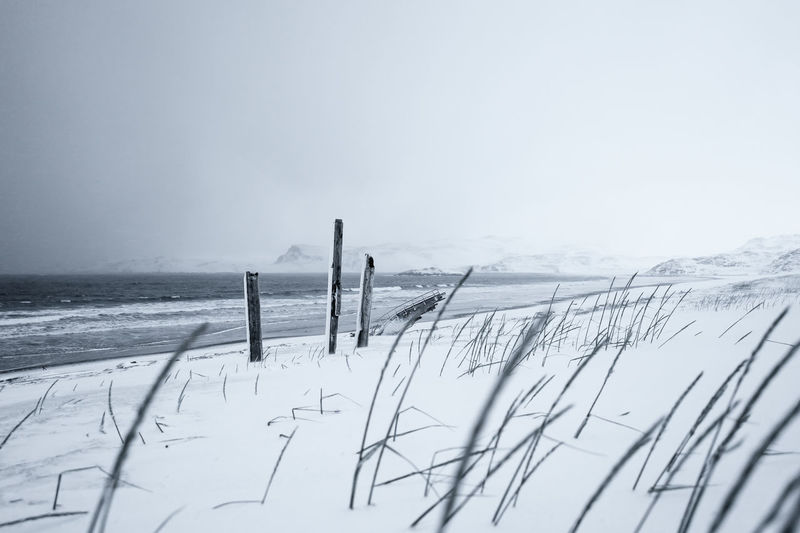 Scenic view of snow covered land by sea against sky