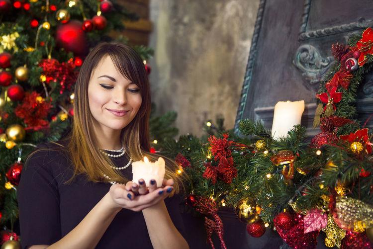 Young woman holding christmas tree