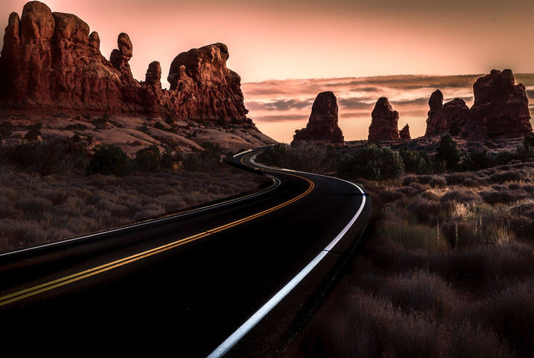 Road amidst rocks against sky during sunset