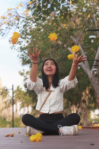 Full length of a smiling girl sitting on plant