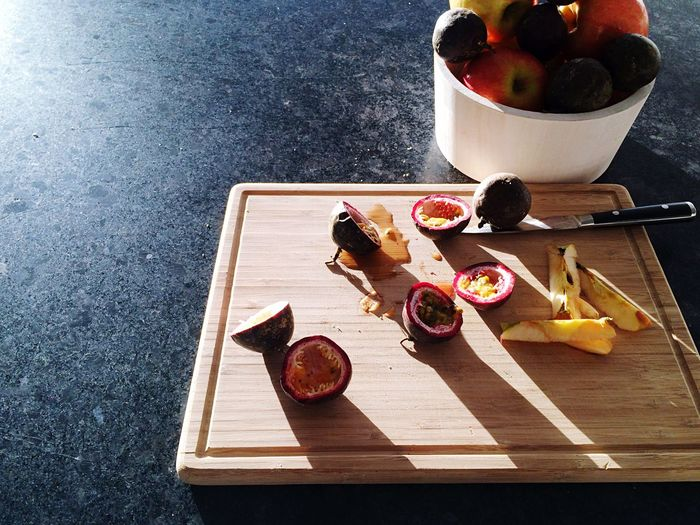 High Angle View Of Sliced Apple And Passion Fruits On Cutting Board