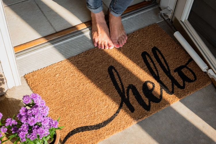 bare feet standing at welcome mat in front entrance of new home Bare Feet Entrance Greeting Hello New Woman Day Doormat Flower Flowering Plant Front Door High Angle View Home Interior House Low Section Mat Mature Adult One Person Plant Real People Shadow Single Word Sunlight Text Welcome