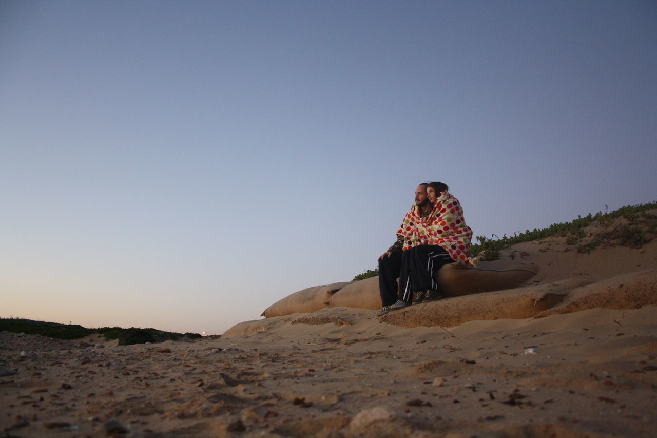 Surface Level Of Couple Wrapped In Blanket Sitting On Rock Against Clear Sky