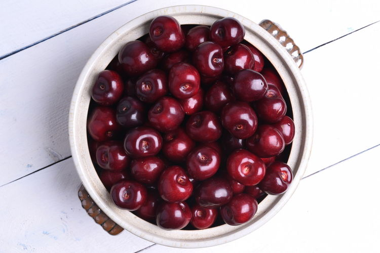 Fresh sweet cherry in bowl on wooden background top view Abundance Bowl Cherry Close-up Container Directly Above Food Food And Drink Freshness Fruit Healthy Eating High Angle View Indoors  Large Group Of Objects No People Red Ripe Still Life Table Temptation Wellbeing