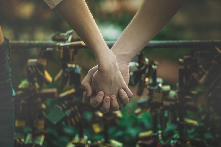 Cropped Image Of Couple Holding Hands Against Padlocks On Railing