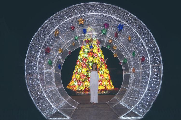 Digital composite image of illuminated ferris wheel against black background