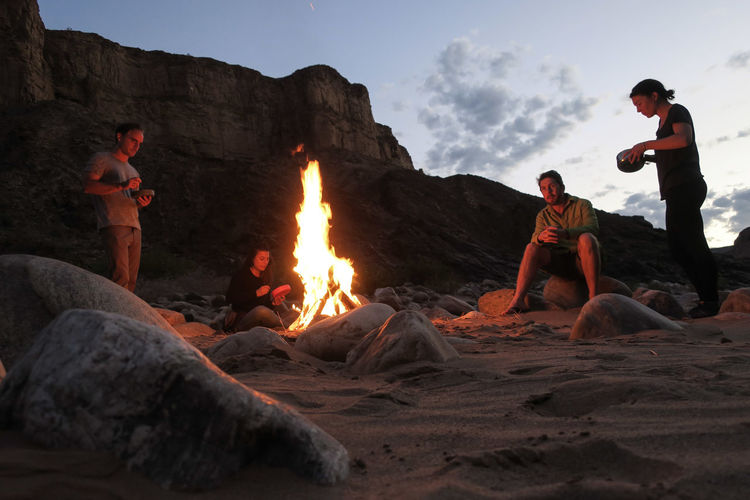 Group of friends enjoying a meal around the campfire Adventure Barbecue Beach Bonfire Campfire Dinner Fire Flame Friends Friendship Group Of People Hikers Let's Go. Together. Meal Mountain Namibia Nature Outdoor Photography Outdoors Rock - Object Sand Team Togetherness Wilderness