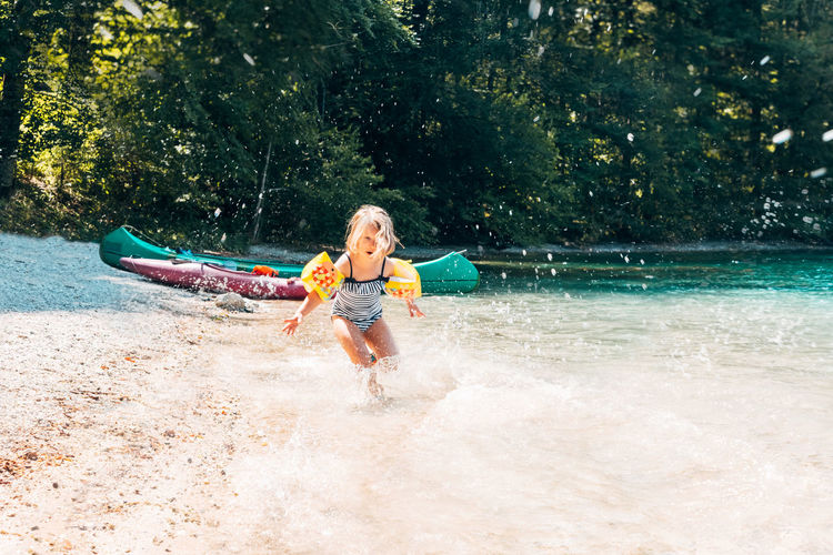 front view of a happy little girl running in a lake water Happy Running Childhood Day Enjoyment Female Full Length Fun Happiness Kayak Land Leisure Leisure Activity Lifestyles Motion Nature One Person Outdoors Plant Play Real People Splash Summer Tree Water