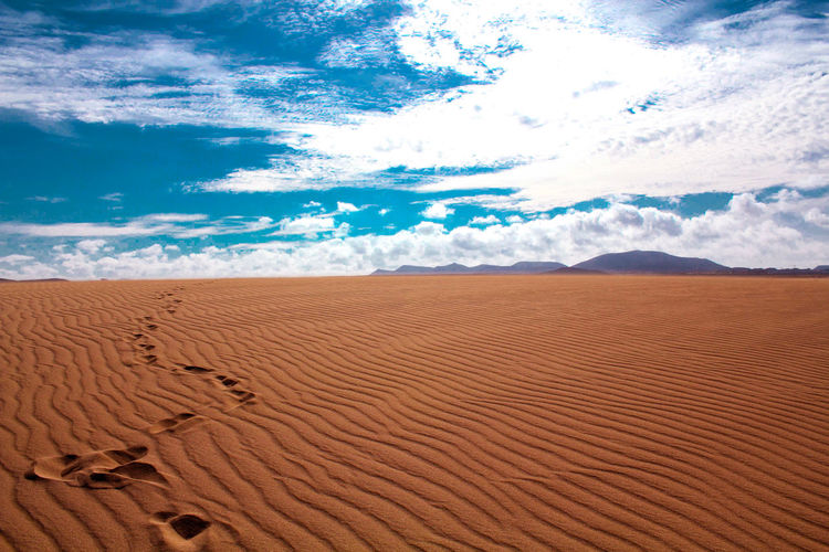 Scenic View Of Sand Dunes Against Dramatic Sky