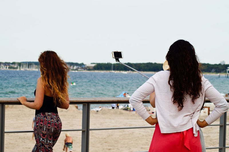 Woman with friends taking selfie by railing at beach