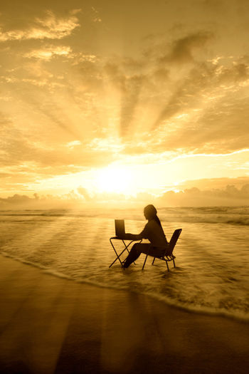 Silhouette woman using laptop while sitting on chair at beach during sunset