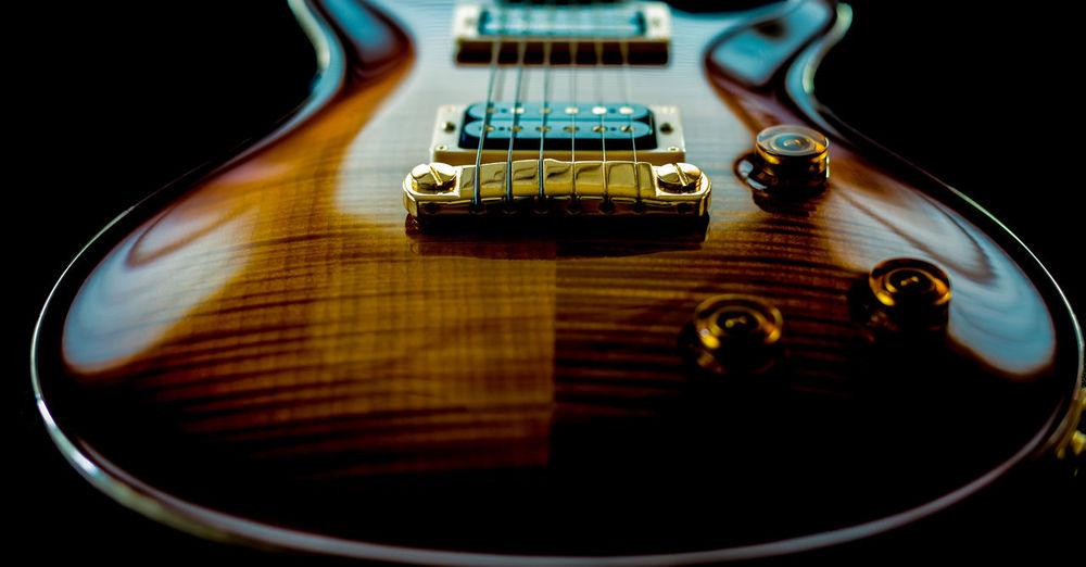 Close-up of guitar over black background