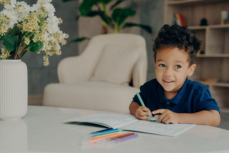 Cute smiling boy writing on book at home