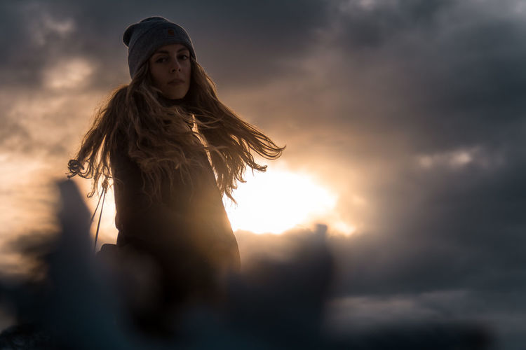 Woman standing against sky during sunset