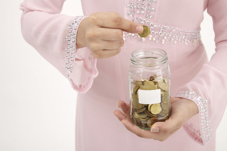 Midsection of woman holding coin over glass jar against white background