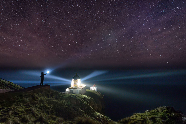 Person holding flashlight while standing on hill against milky way