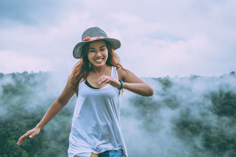 Smiling young woman standing against sky