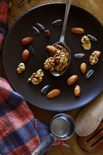walnut, almond nuts and sunflower seeds on a plate Sunflower Seed Sunflower Seeds Superfood Spoon Utensils Plate Kitchen Kitchen Utensil Table Food Food And Drink Taste Flavor Ingredient Ingredients Nuts Nut - Food Flavor Fruit Nut - Food High Angle View Food And Drink Peanut - Food Dried Fruit Dried Food Almond Walnut