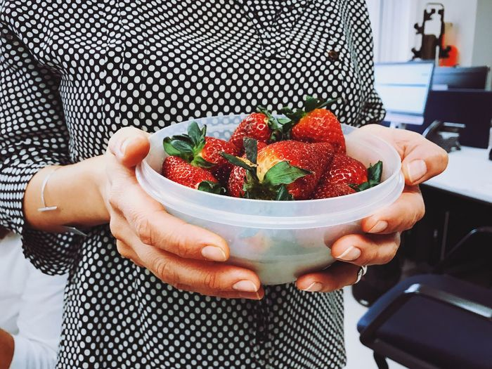 Midsection of woman holding bowl with strawberries