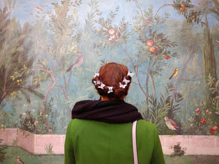 Rear view of woman standing in front of mural