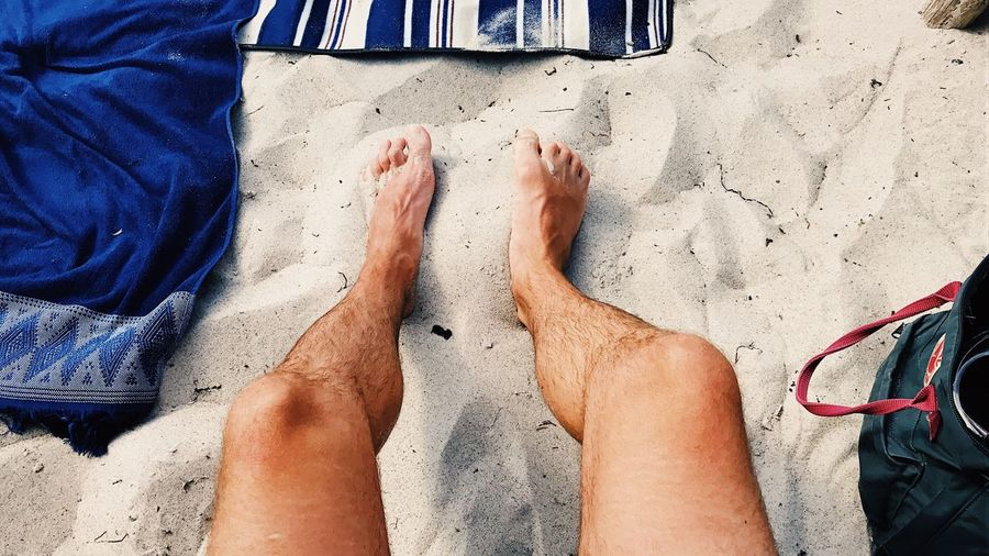 Low section of men sitting on sand