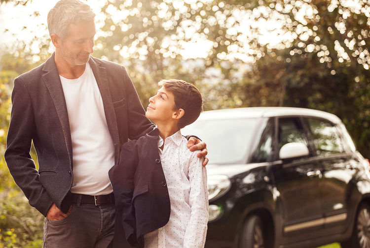 Smiling Man Looking At Son Against Car On Road