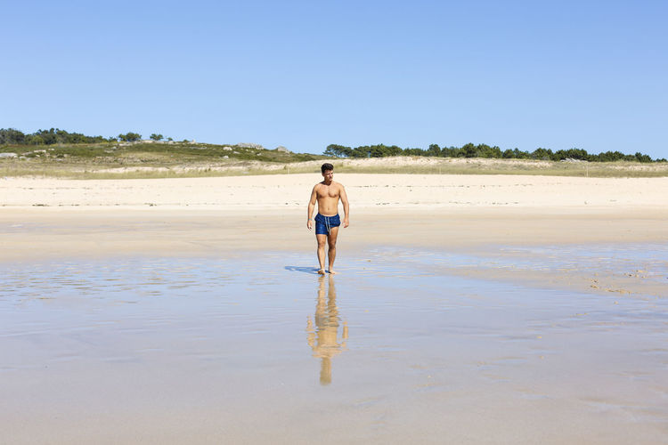 Full length of shirtless man standing on beach against clear sky