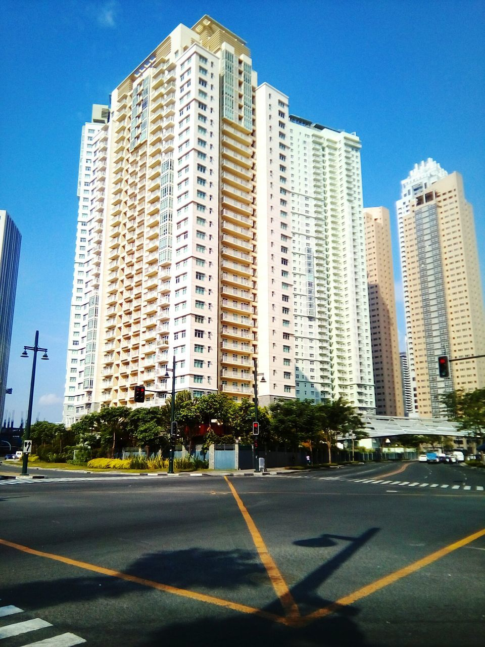 architecture, road, built structure, building exterior, city, skyscraper, street, transportation, day, car, outdoors, tree, clear sky, sky, growth, no people, modern, cityscape