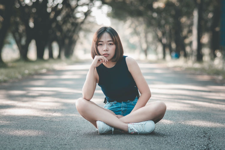 Asian Girl Asian Teen Beautiful Woman Casual Clothing Day Focus On Foreground Front View Full Length Hairstyle Leisure Activity Lifestyles Looking At Camera Nature One Person Outdoors Portrait Real People Road Sitting Teenager Young Adult Young Women