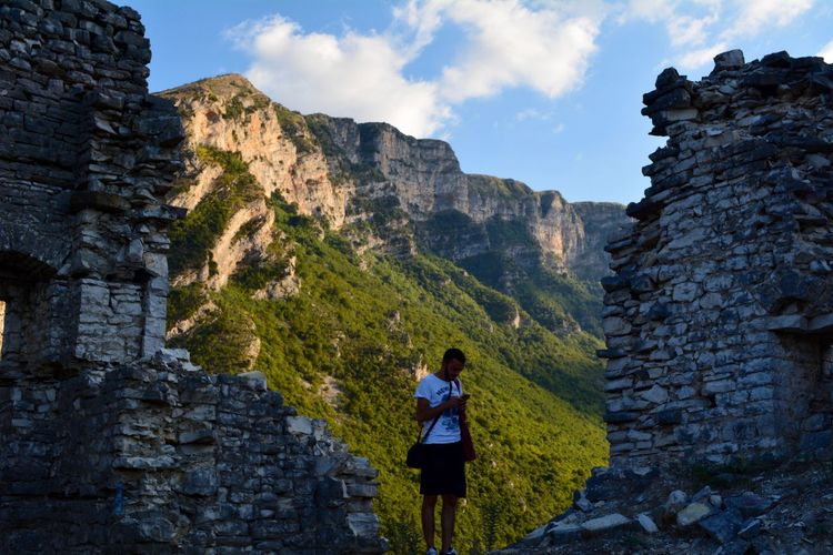 Man using phone amidst stone wall against mountain