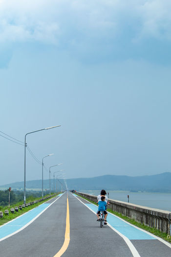 Rear view of mother and son riding bicycle on road against sky