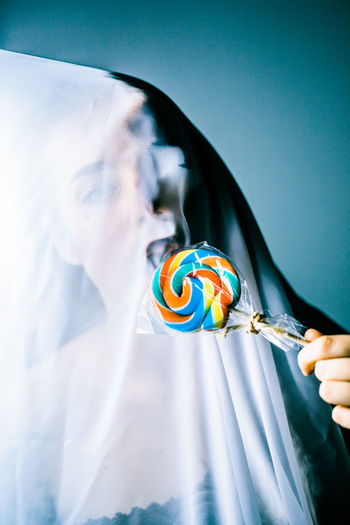 Portrait of woman in textile eating lollipop