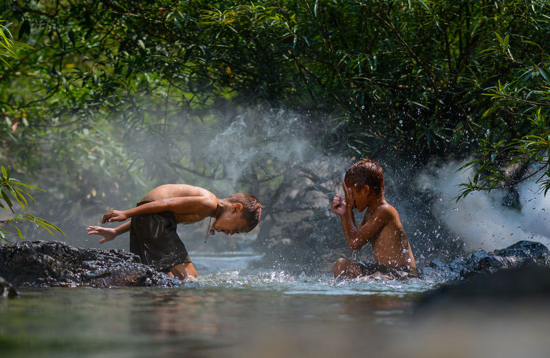 Side view of shirtless brothers bathing in river at forest
